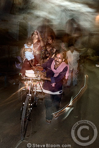Family travelling on bicycle rickshaw at night, Varanasi, India