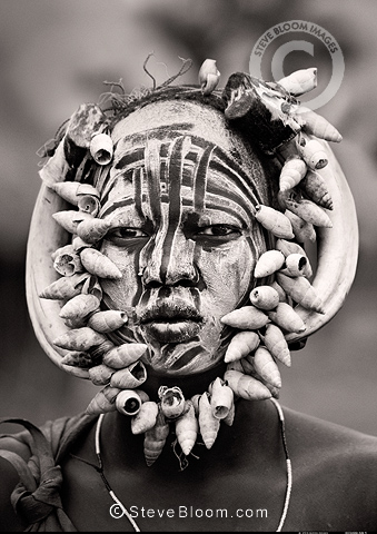 Mursi tribeswoman adorned with animal horns, shells and white clay. Omo Delta, Ethiopia, Africa.