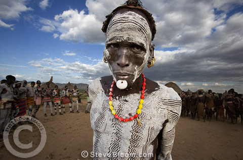 Karo tribesman encircled by tribe, with traditional clay body painting, clay and feather headddress. Omo Delta, Ethiopia, Africa.