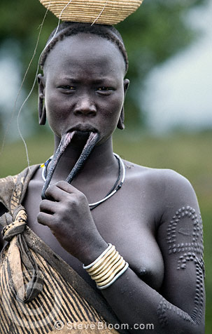 Mursi tribeswoman stretching her lower lip into which a lip plate is inserted, Omo Delta, Ethiopia, Africa.