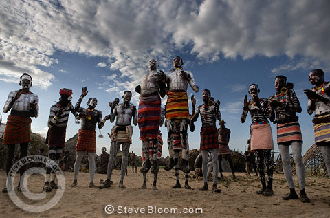 Karo tribesman dancing in the circle, both with feet off the ground, Omo Delta, Ethiopia, Africa.