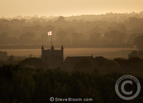 Flag flying on the church at dusk, Wye village, Kent