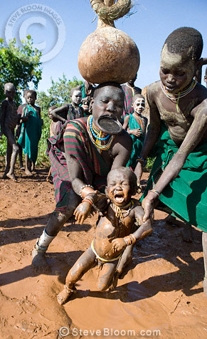 Boy lifted out of mud in which he was playing, Suri tribe, Omo Delta, Ethiopia