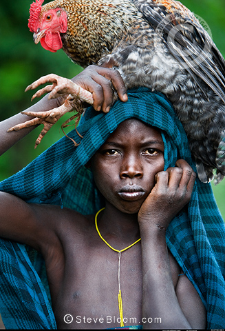Suri boy with chicken, Omo Delta, Ethiopia.