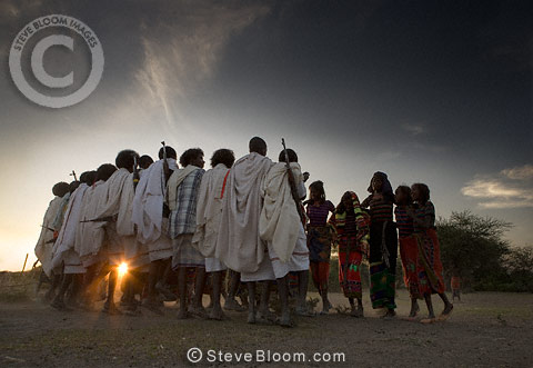 Men, wearing white, dancing with a group of young women, Afar tribe, Ethiopia