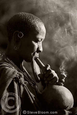 Suri tribeswoman with clay lip plate, smoking, Omo Delta, Ethiopia