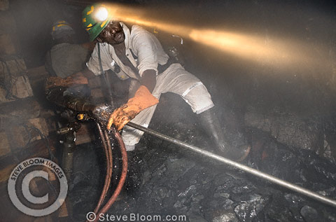 Gold miner at work drilling underground rock face, near Johannesburg, South Africa