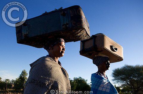 Ndebele women carrying suitcases balanced on their heads, South Africa