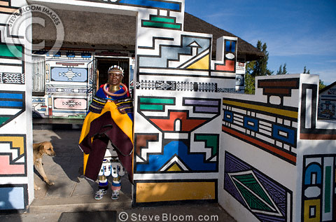 Ndebele woman outside her traditionally decorated house, South Africa