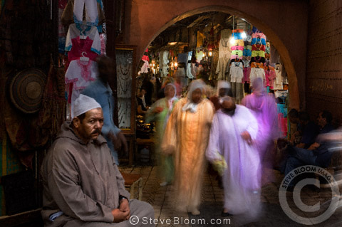 Stall vendor and browsing visitors in the Djemaa el Fna souq in Marrakech, Morocco