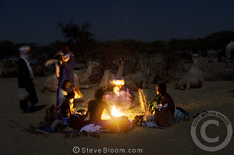 People gathered around a campfire at night during the Gerewol festival, north of Abalak, Niger
