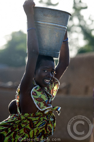 Woman carrying a bucket of water on her head with a baby strapped to her back, near Djenne, Mali