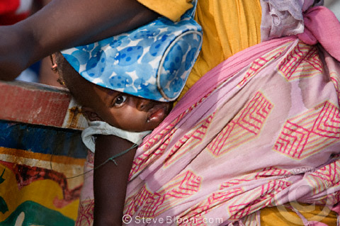 Child strapped to her mother's back at the fish market, Yoff, Dakar, Senegal, west Africa