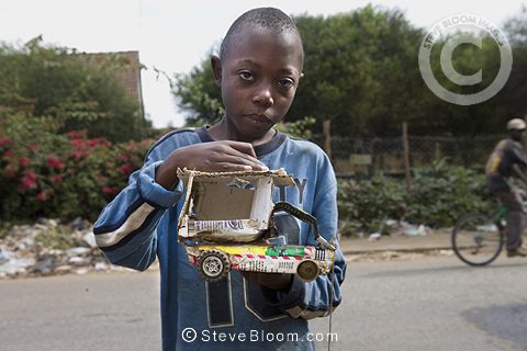Boy with a toy car he has made, Nairobi, Kenya.