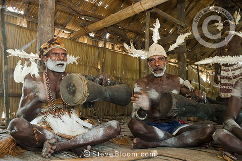 Men from the Asmat Tribe playing drums and singing, Agats village, New Guinea, Indonesia.