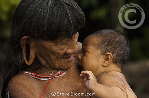 Huaorani Indian woman holding baby. Gabaro Community, Yasuni National Park, Amazon rainforest, Ecuador, South America.