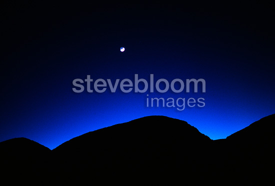 Crescent moon setting over sand dunes, Big Bend National Park, Texas, USA