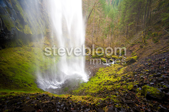 A view from behind one of the many gorgeous waterfalls along Eagle Creek Trail, Columbia River Gorge, Oregon, USA