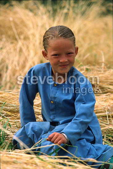 Young Ladakhi girl smiling sitting in a field India