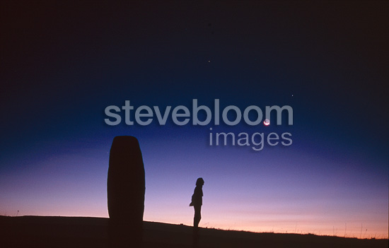 Man and Moon rising close to a menhir Lozere Mount