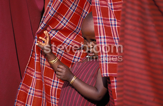 Masai child hidden in the clothing of an adult Tanzania