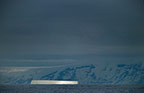 Stormy sky showing iceberg lit up by a shaft of sunlight,  Antarctica