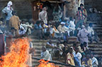 Crowds beside a funeral pyre at the cremation ghats on the banks of the Ganges, Varanasi, India
