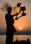 Hindu holy man performing a religious ceremony (puja) to celebrate sunrise on the banks of the Ganges, Varanasi, India