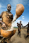 Karo woman winnowing grain by pouring it from one gourd to another. Omo Delta, Ethiopia, Africa