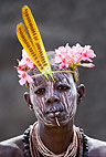 Young Karo tribeswoman wearing head-dress of adenium flowers and delonix seed pods. Omo Delta, Ethiopia, Africa.