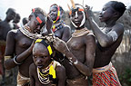 Young Karo girls decorating each others' hair, Omo Delta, Ethiopia, Africa