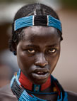 Girl from the Hamar tribe wearing traditional bead headdress and necklaces, Dimeka market, Omo Delta, Ethiopia, Africa.