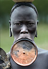 Mursi tribeswoman with large clay lip plate through lower lip, balancing basket on her head. Omo Delta, Ethiopia, Africa.