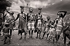 Group of Mursi women and children in their village. Omo Delta, Ethiopia, Africa.