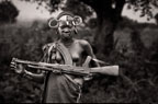 Young woman of the Mursi tribe, with a rifle slung around her neck, Omo Delta, Ethiopia, Africa.