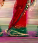 Woman wearing colorful sari, walking on coloured paper at Elephant festival, Jaipur.