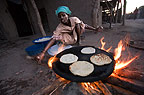Woman from Afar tribe making ga'ambo maize flat-bread, Bilen, Ethiopia