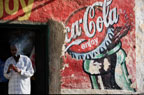 Man smoking in doorway of shop with painted Coca Cola sign, Harar, Ethiopia