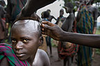 Boy of the Suri Tribe having his head shaved, Omo Delta, Ethiopia.