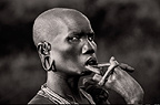 Suri tribeswoman playing with lip stretched to take a lip plate, Omo Delta, Ethiopia