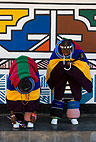 Ndebele women in tribal dress outside a traditionally painted house, South Africa