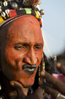 Wodaabe men looking in the mirror at his kohl lips during the Gerewol Festival, north of Abalak, Niger