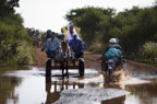 Crossing a flooded road by motorbike and donkey cart on the way to the market at Djenne, Mali
