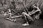 Young Suri boy picking thorns from the foot of an elder tribesman, Omo Delta, Ethiopia