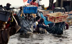 Traders collecting fish from returning fishing boats, Joal, Senegal