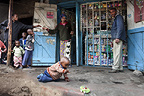 Child playing with a toy car outside Gathama's Shop, Nairobi, Kenya.
