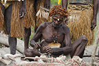 Man from the Asmat Tribe carving with a chisel, Agats village, New Guinea, Indonesia