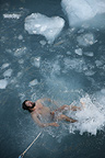 Guide taking Arctic plunge, among ice-floes, Svalbard, Norway