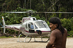 Huaorani Indian, Menga Darita, with helicopter. Gabaro Community, Yasuni National Park, Amazon rainforest, Ecuador, South America.