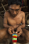 Huaorani Indian, Tage Kaiga, making feather crown. Gabaro Community, Yasuni National Park, Amazon rainforest, Ecuador, South America.
